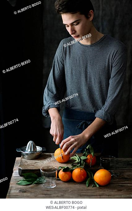 Young man cutting oranges