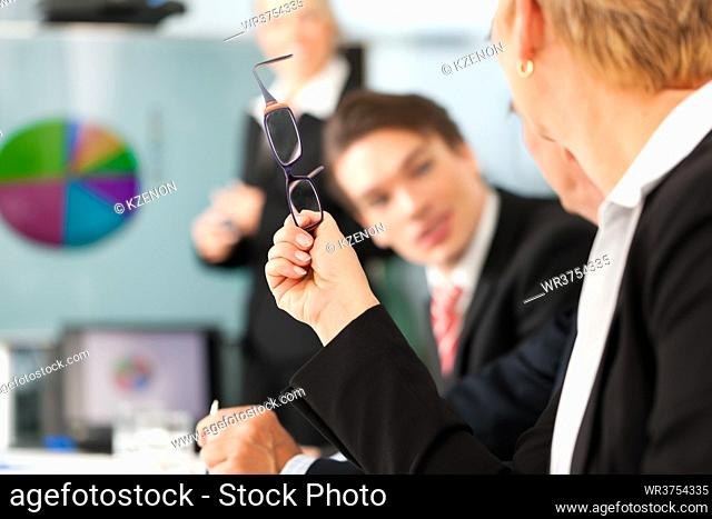 Business - presentation within a team, a female colleague is standing on the screen