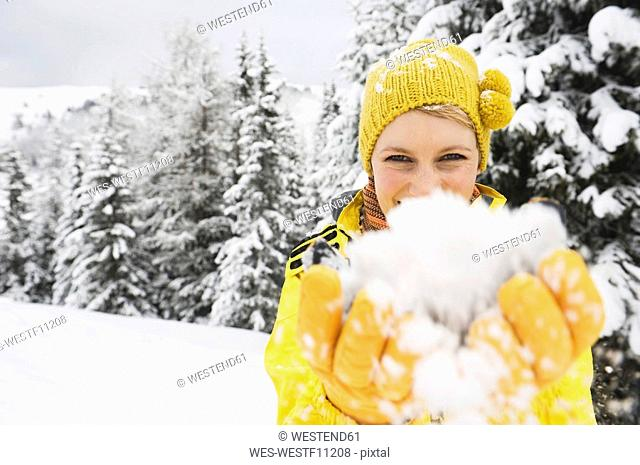 Italy, South Tyrol, Young woman fooling about with snow, portrait