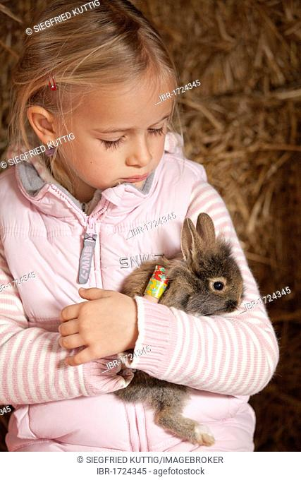 Young girl cuddling with a rabbit
