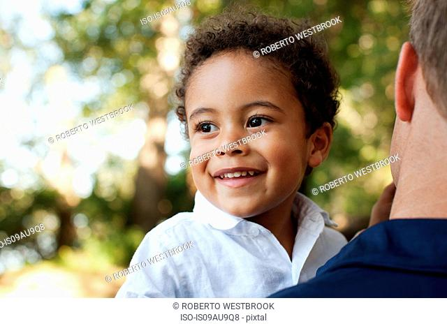 Over shoulder view of father carrying preschool boy looking away smiling