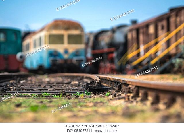 Shallow depth of field closeup of the rail tracks with old disused locomotives and carriages in the background