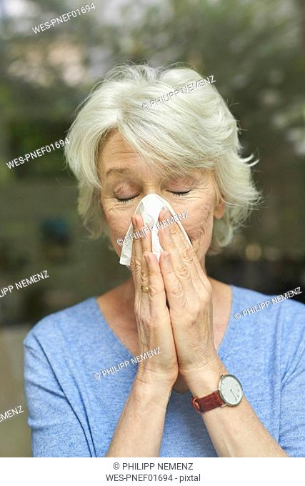 Mature woman blowing nose