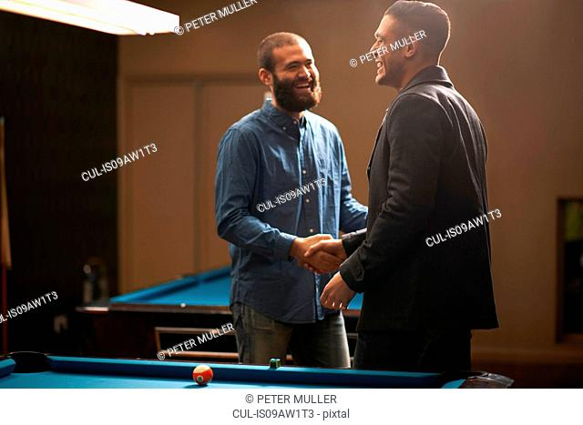 Men shaking hands at pool table