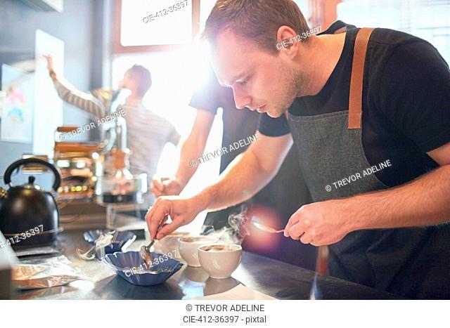 Focused male coffee roaster testing coffee