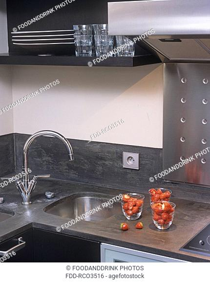 A detail of a modern kitchen, sink, three glasses of strawberries