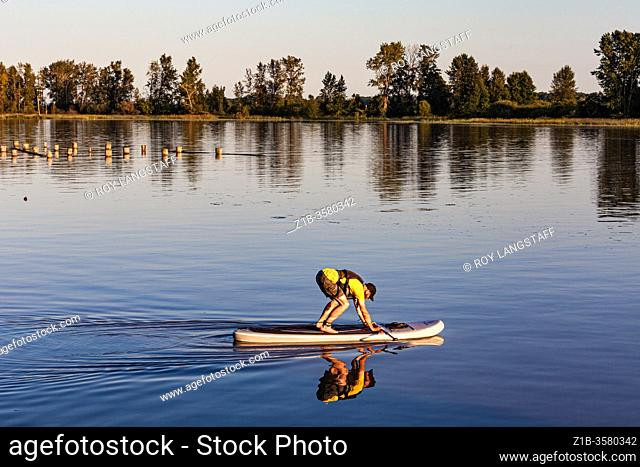 Preparing to stand up on a paddleboard after passing under a low bridge at high tide