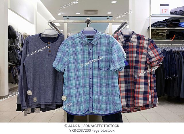 Close-up of blouses, shirts hanging on rack in retail shop. Store interior