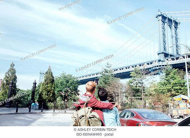 Rear view of male couple taking selfie in front of Manhattan Bridge, New York, USA