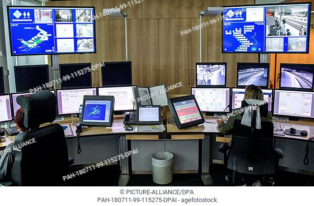 11 July 2018, Germany, Hamburg: An employee of the Deutsche Bahn (GermanRailway) works in front of screens at the control centre of the Hamburg S-Bahn