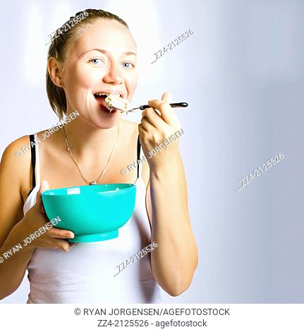 Smiling girl consuming yoghurt and muesli for breakfast on kitchen wall copy space