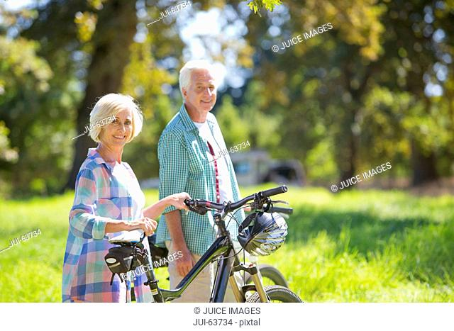 Portrait of senior couple with mountain bikes in treelined field