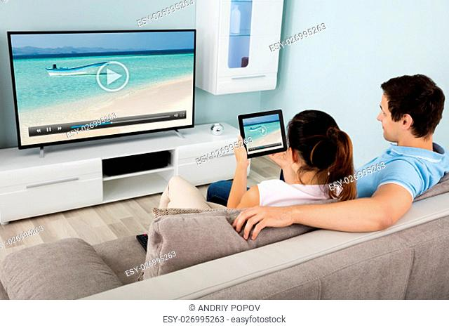 Young Couple Connecting Television Channel Through Wi-fi On Digital Tablet At Home