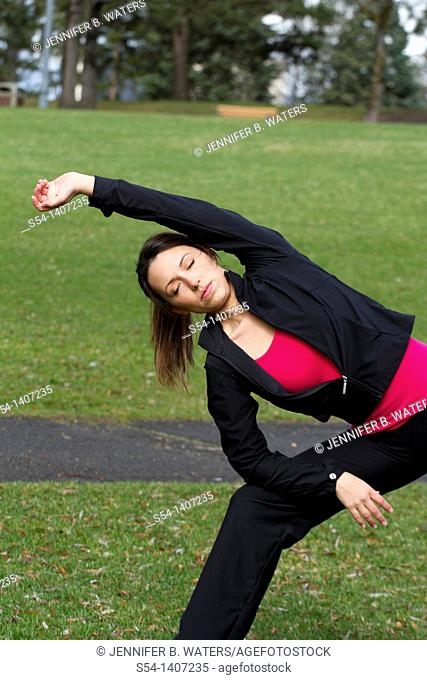 A young woman stretching before exercising in Riverfront Park, Spokane, Washington, USA