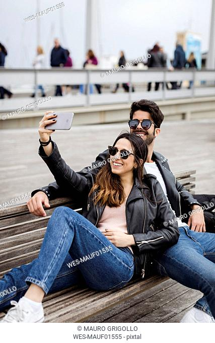 Spain, Barcelona, happy young couple resting on a bench taking a selfie