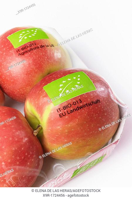 Wrapped pink lady organic certified apples in white background