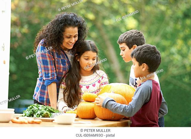 Mature mother and three children admiring homegrown pumpkins in kitchen
