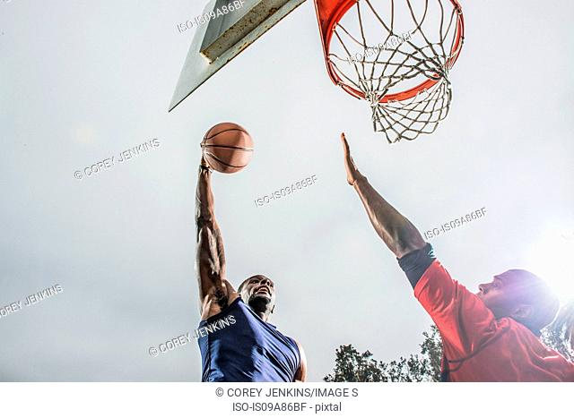 Young basketball players jumping to score hoop
