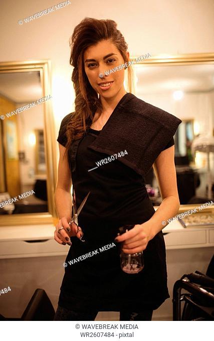 Female hairdresser holding scissor and spray bottle