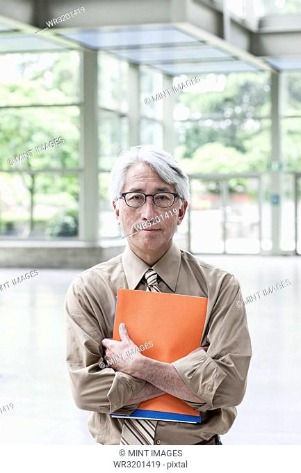 A portrait of an Asian businessman in a convention centre setting