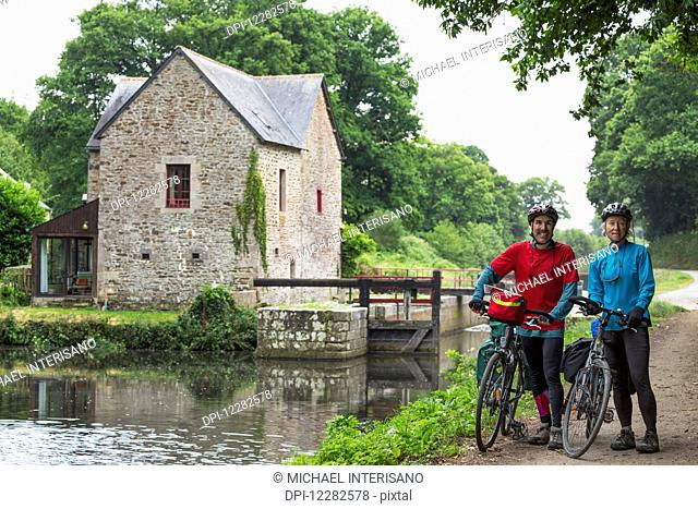 Couple with bikes on a path along a canal with lock and stone lock house in the background; Gaec Grand Boutron, Calorguen, Brittany, France