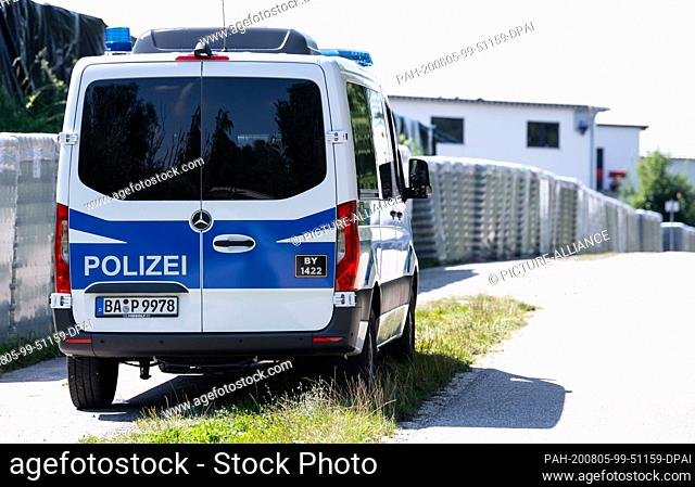 05 August 2020, Mamming: A police car is parked outside a cannery. The number of corona infected people in Mamming continues to rise: 166 of 600 employees of a...