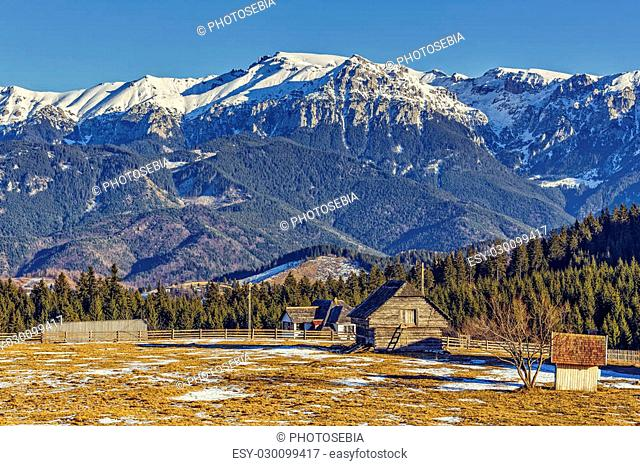 Winter rural landscape with snowy Bucegi mountains ridge, meadow enclosure and wooden barn in Fundata village, Brasov county, Romania