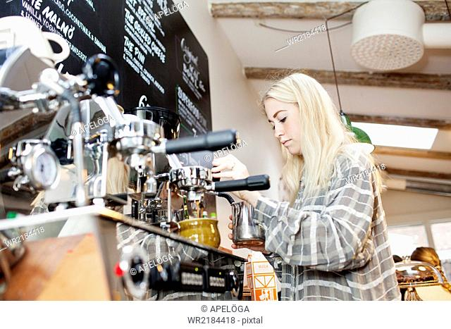 Young female barista making coffee in cafe