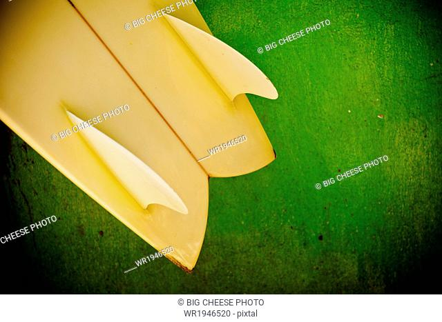Close up of a yellow twin fin swallowtail surfboard