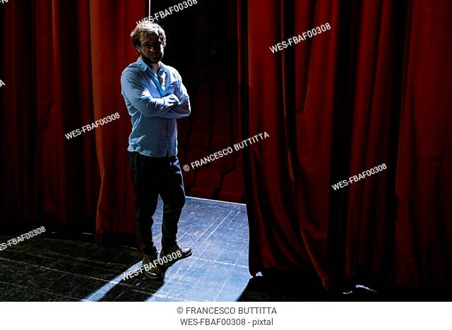 Portrait of man standing on theatre stage