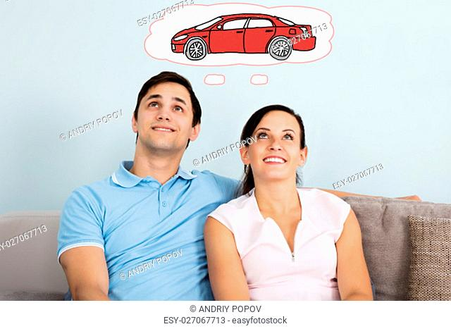 Young Happy Couple Dreaming Of Having Car While Sitting On Sofa