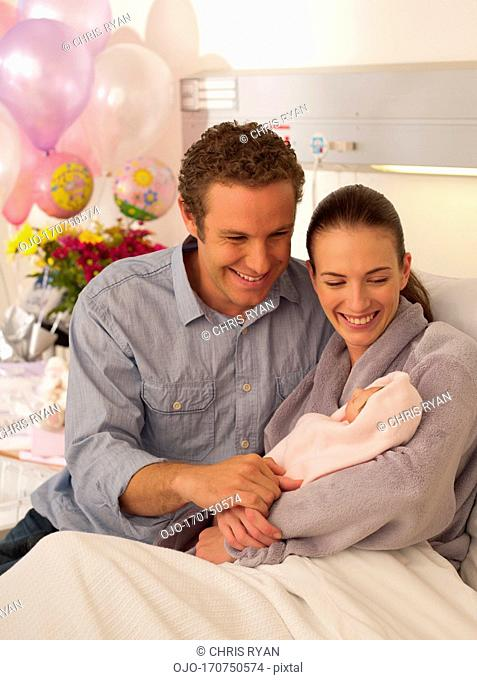 Couple holding newborn baby in hospital