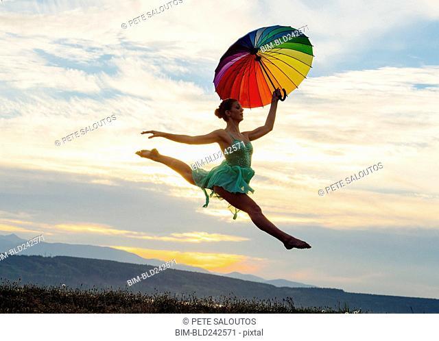Caucasian ballerina jumping with multicolor umbrella