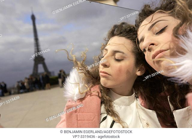woman with mirror outdoors, double self, in city next to tourist sight Eiffel Tower, at Espl. du Trocadéro, in Paris, France