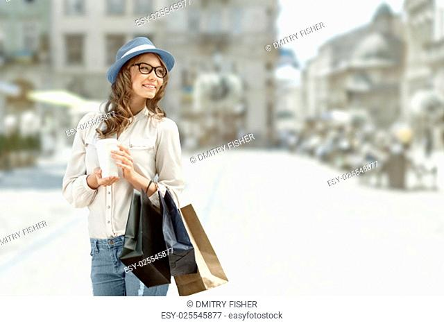 Happy young fashionable woman taking a coffee break after shopping, smiling with a coffee-to-go in her hands against urban background