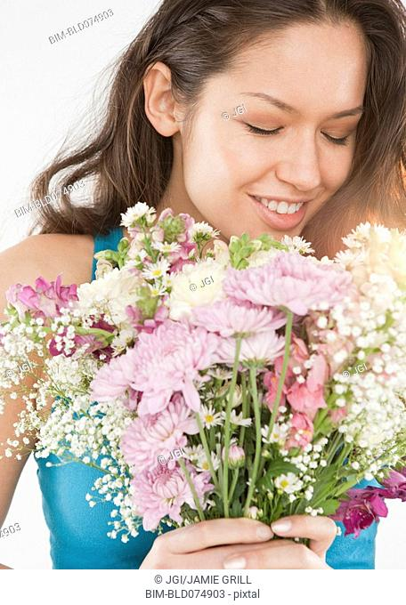 Mixed race woman holding bouquet of flowers