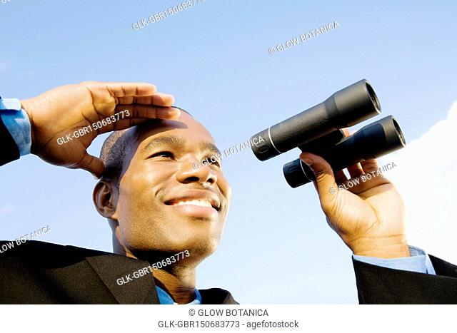 Close-up of a businessman holding binoculars and smiling