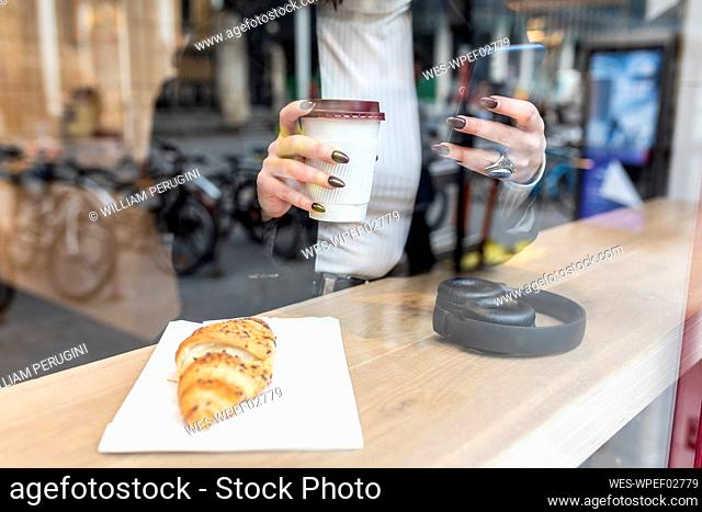 Close-up of businesswoman having a coffee break and using mobile phone at a cafe in the city