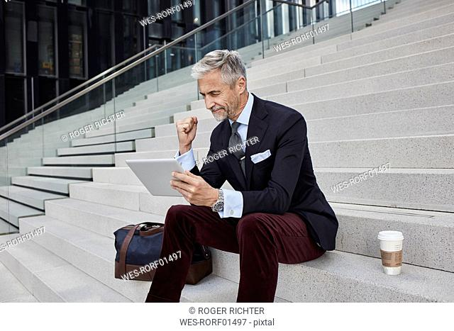 Fashionable businessman with travelling bag nd coffee to go sitting on stairs using tablet