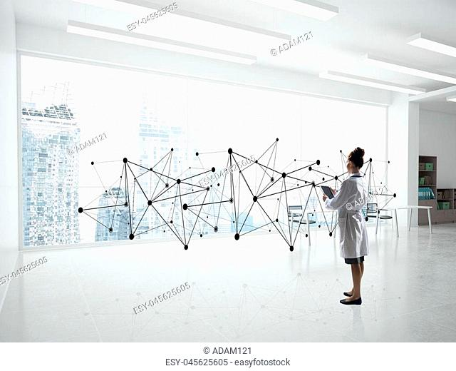 Horizontal shot of confident woman doctor in white medical suit standing in bright hospital office and interracting with network structure