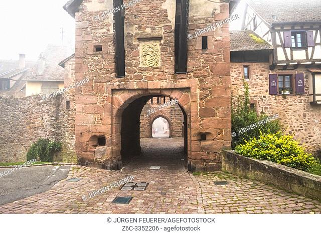 medieval rampart and town gate of village Riquewihr with fog, Alsace, France, touristy village of the Wine Route