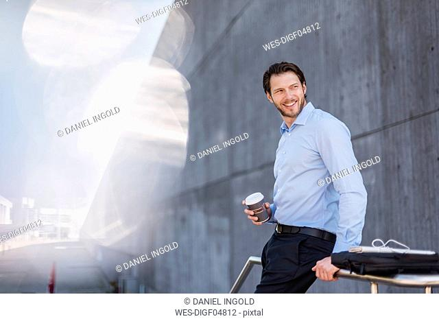 Smiling businessman with laptop bag and takeaway coffee leaning against a railing