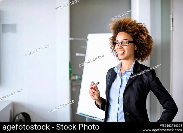 Smiling businesswoman leading a presentation at flip chart in office