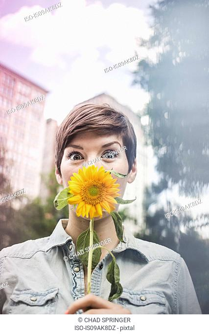 Woman covering mouth with flower
