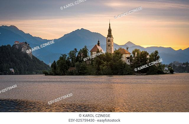 Little Island with Catholic Church in Bled Lake, Slovenia at Sunrise with Castle and Mountains in Background