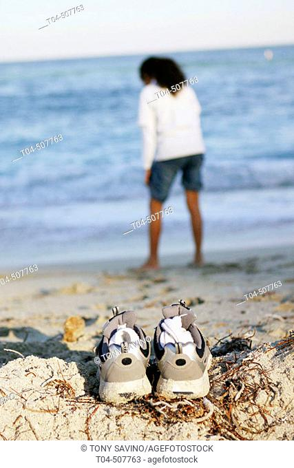 10-year-old biracial girl at beach, sneakers on sand. Miami, Florida, USA