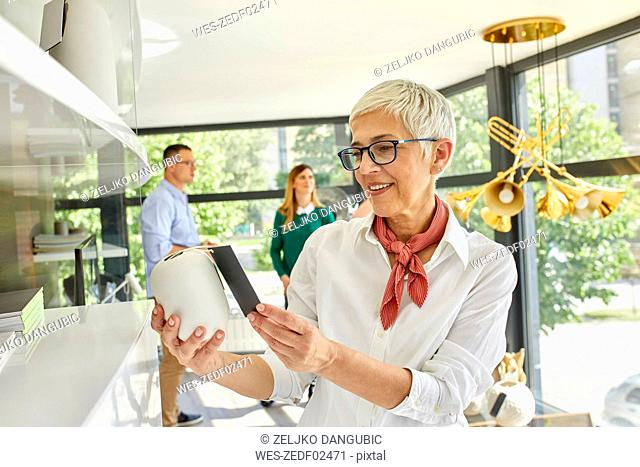 Mature woman looking at vase in a showroom