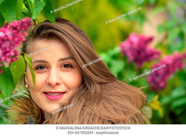 Young girl posing near lilac bushes