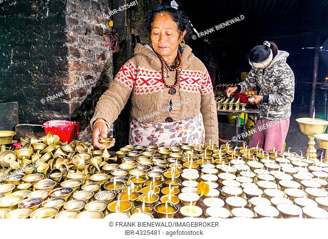A woman is arranging butter lamps at a temple in Boudha, Kathmandu, Nepal