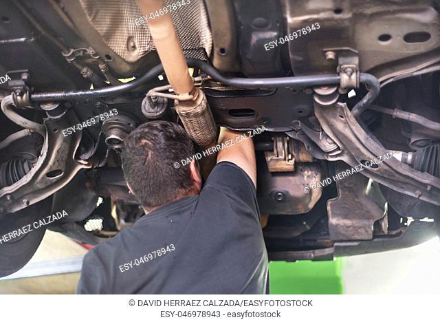 Mechanic repairing exhaust system . Car repair service